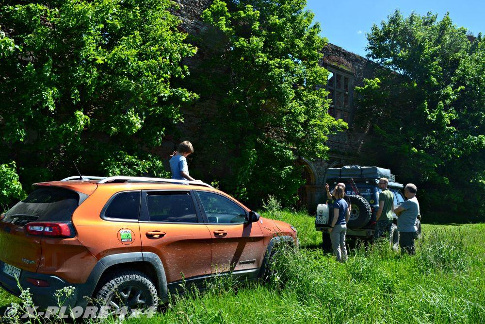 auta terenowe przed ruinami pałacu